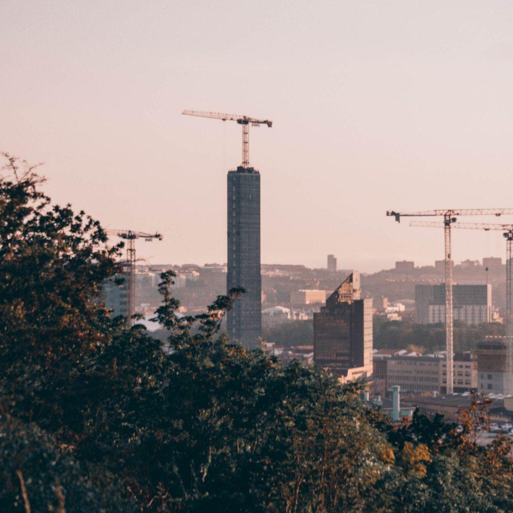 dimmig bild över stad med lyftkranar och träd